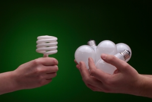 Man trading a bunch of incandescent light bulbs for one compact flourescent. Focus on bulbs. Green background.